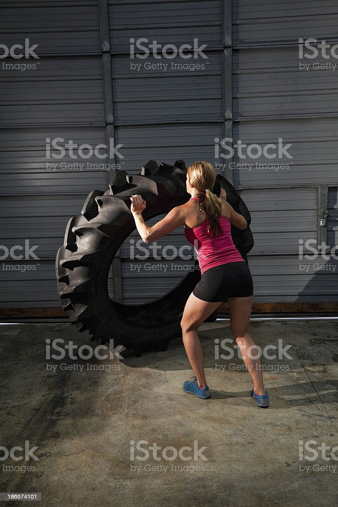 Woman strength training with tractor tire stock photo