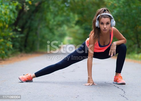 Smiling woman stretch muscles at park. Athletic exercising outdoor.
