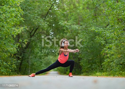 Smiling woman stretch muscles at park. Athletic exercising outdoor. Fitness and health concept