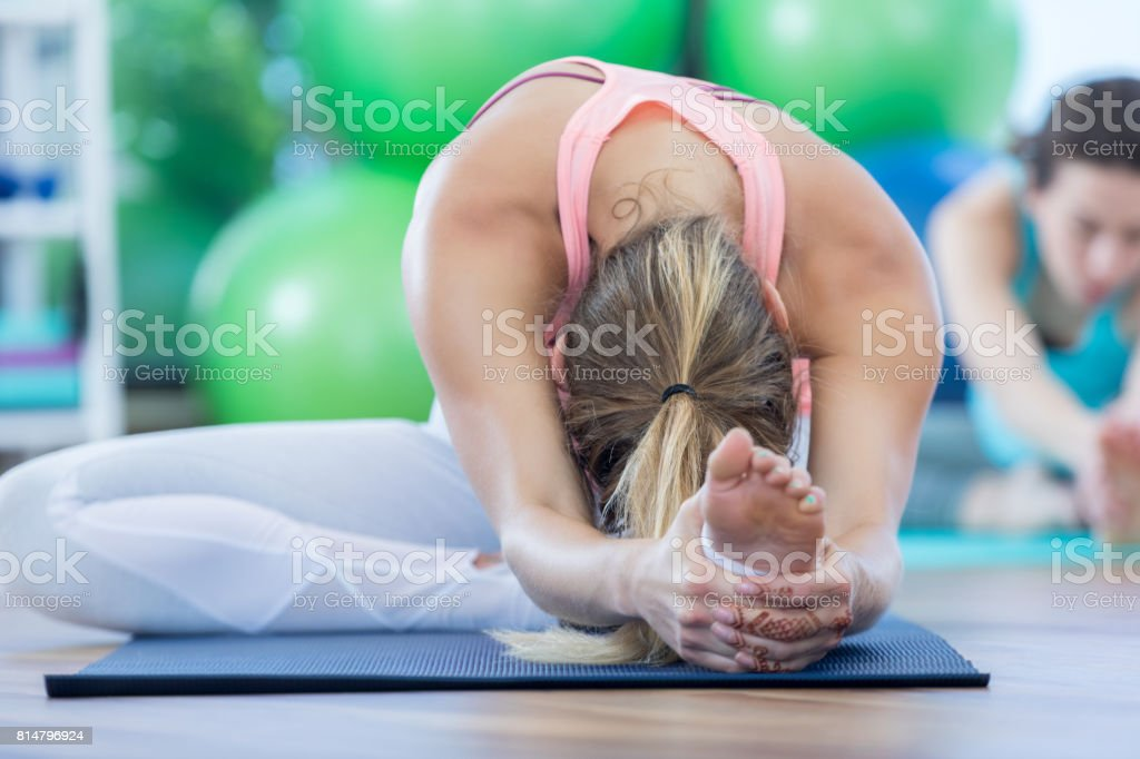 Woman stretches out and touches toes stock photo