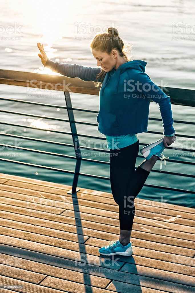 Woman stretching after outdoor training, sunset time stock photo