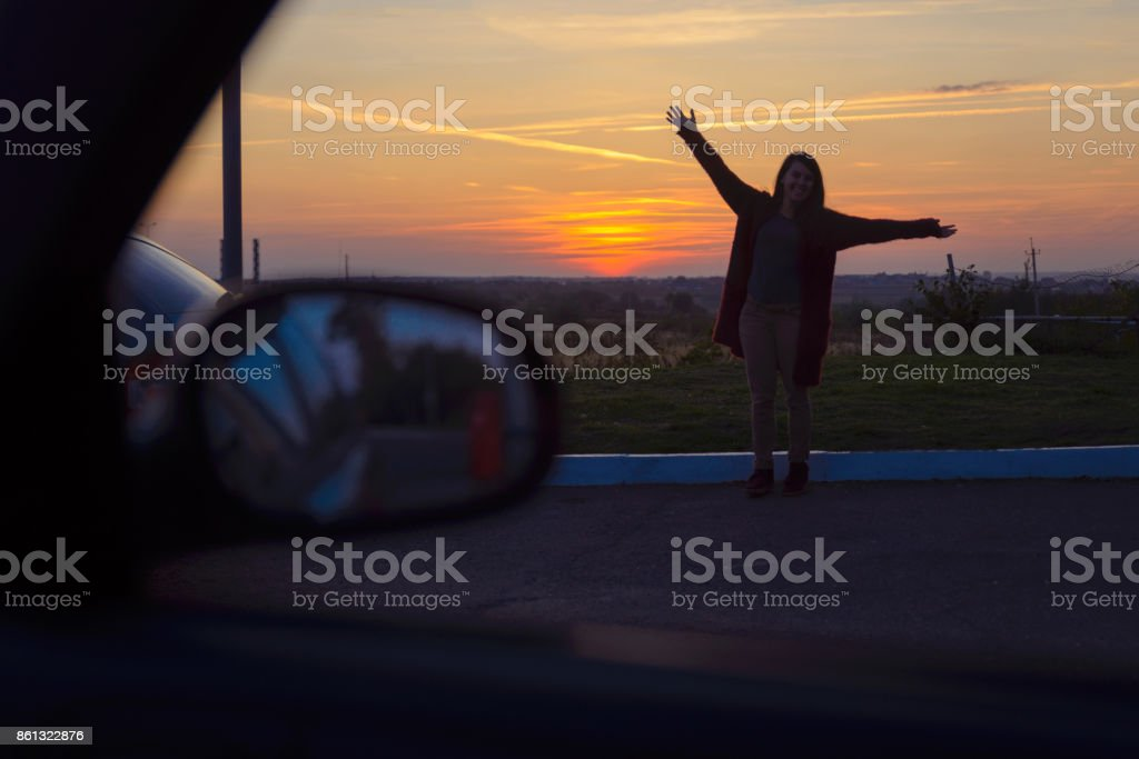 woman stretching aftet long trip in car on sunset stock photo