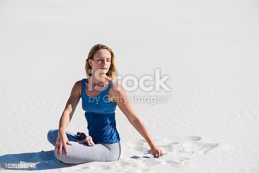istock Woman stretching and relax in desert sand 1039188746