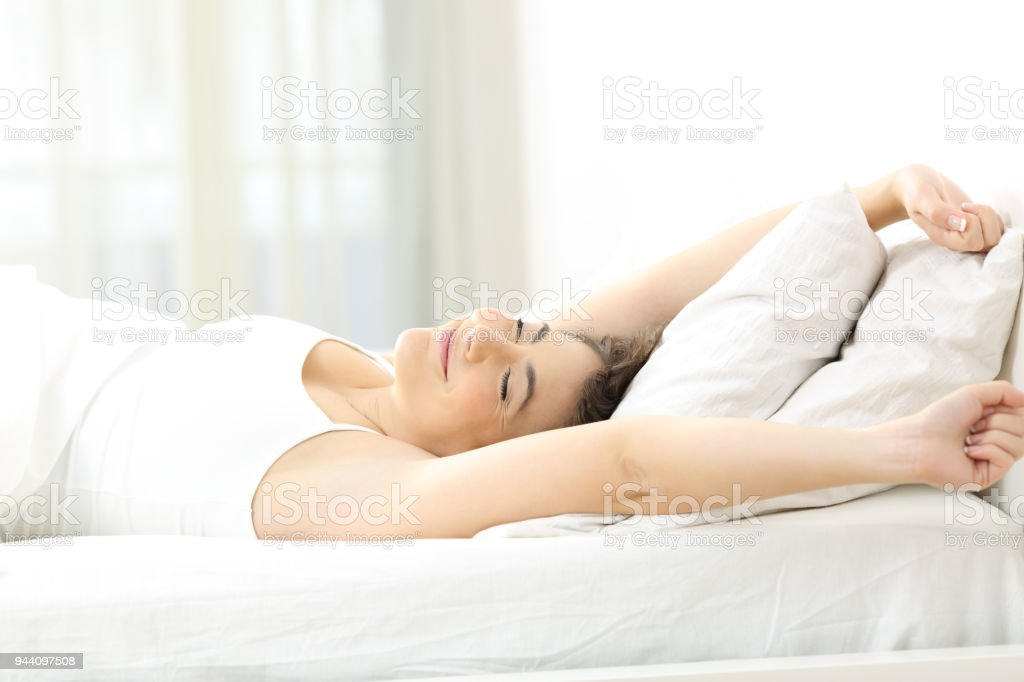 Woman stretching arms in the moring on the bed stock photo