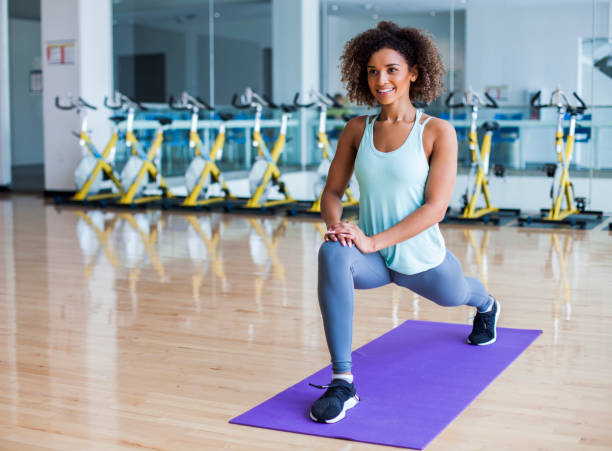 woman stretching at the gym - lunge stock photos and pictures