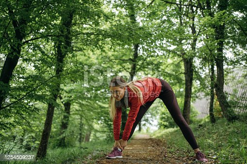 Smiling woman stretching before training in nature.