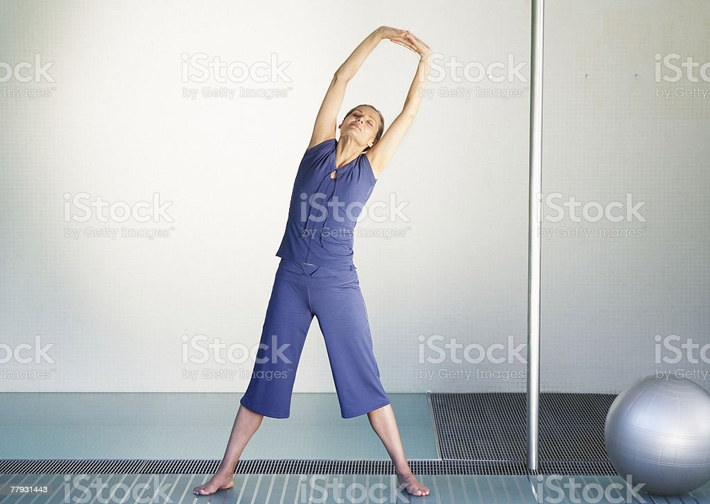 Woman stretching beside a pilates ball royalty-free stock photo