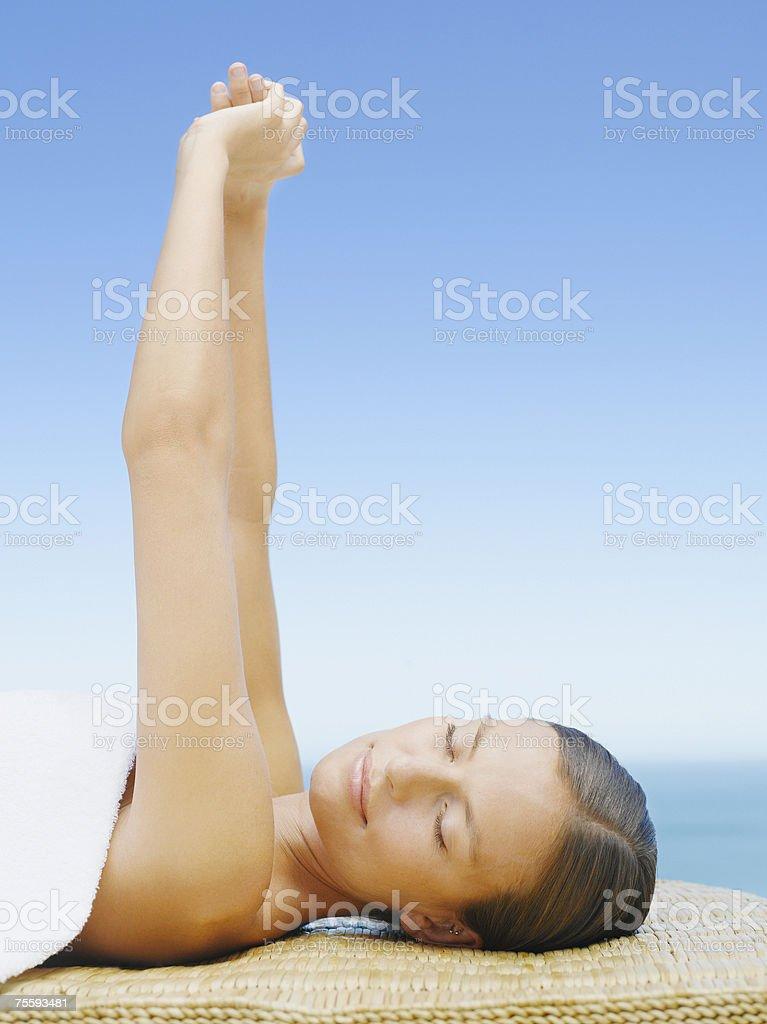 Mulher, esticar o braço para fora sobre uma Mesa de Massagem foto de stock royalty-free