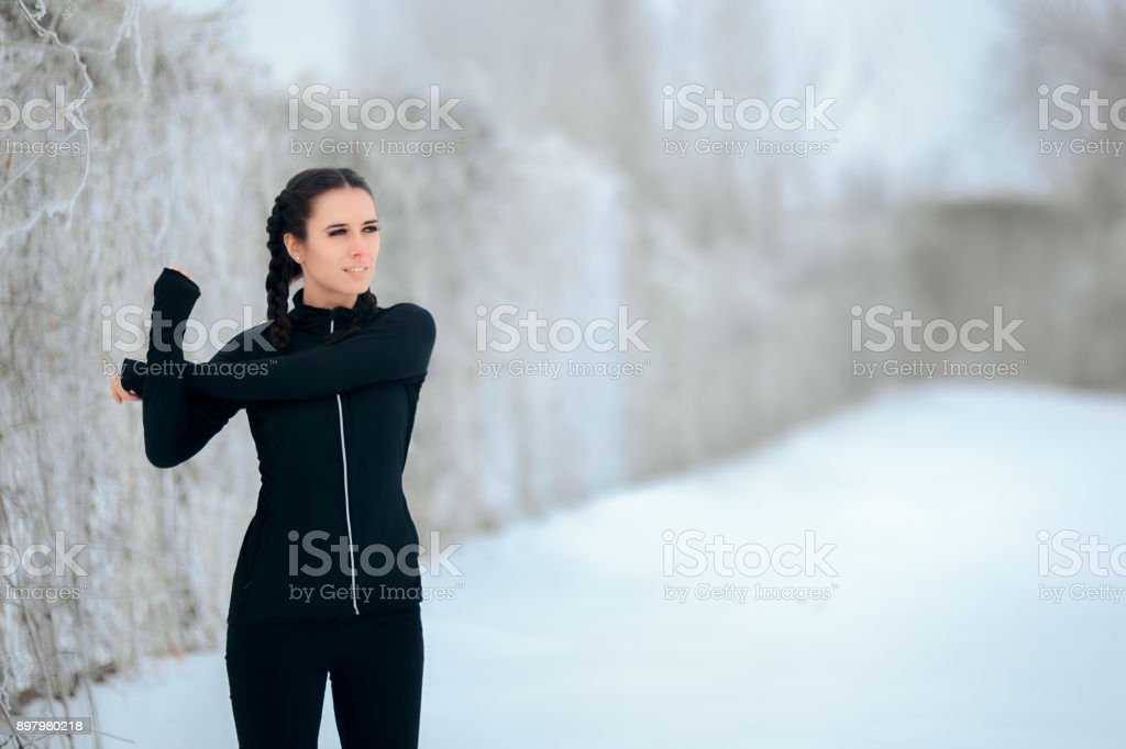 Woman Stretching her Arms Ready to  Exercise Outdoor in Winter Season stock photo