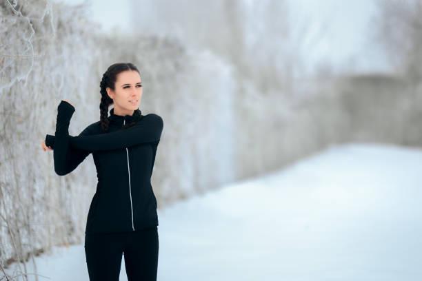 frau, dehnen ihre arme bereit, bewegung im freien im winter - immunsystem stärken stock-fotos und bilder