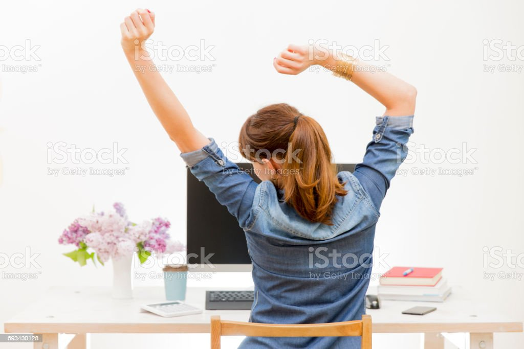 Woman stretching her arms sitting by the table at work next to computer