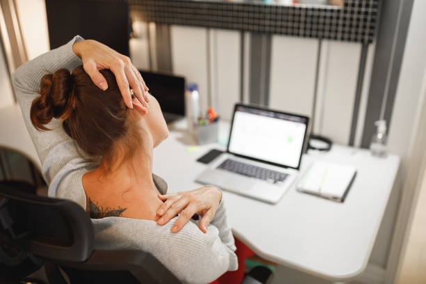 Woman stretching her neck while working at home stock photo