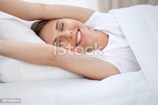 istock Woman stretching in bed after wake up, entering a day happy and relaxed after good night sleep. Sweet dreams, good morning, new day, weekend, holidays concept 687698540