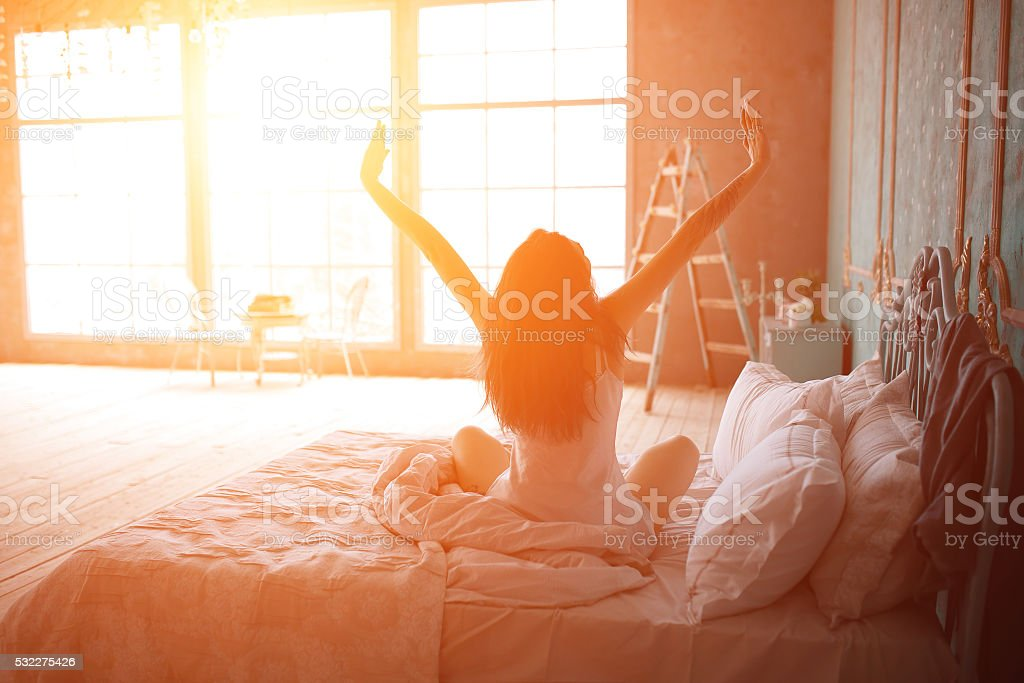 Woman stretching in bed after wake up royalty-free stock photo
