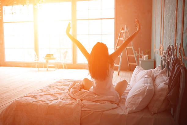 femme étirer au lit après réveillez-vous - matin photos et images de collection