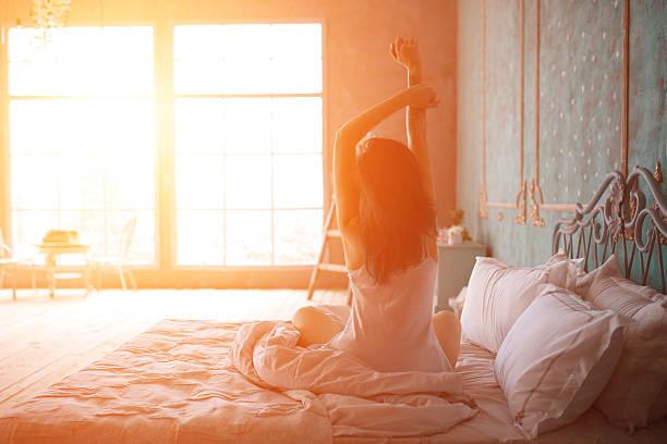 Mulher de alongamento depois de acordar na cama - foto de acervo