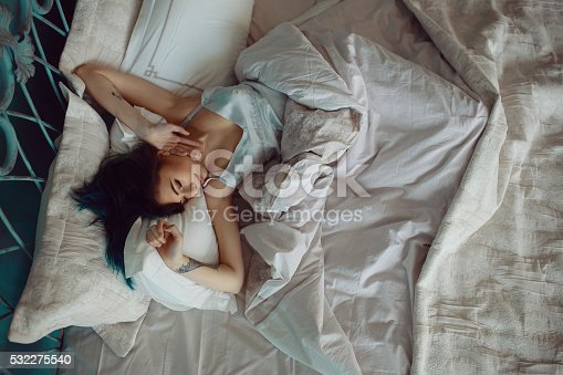 532275426 istock photo Woman stretching in bed after wake up 532275540