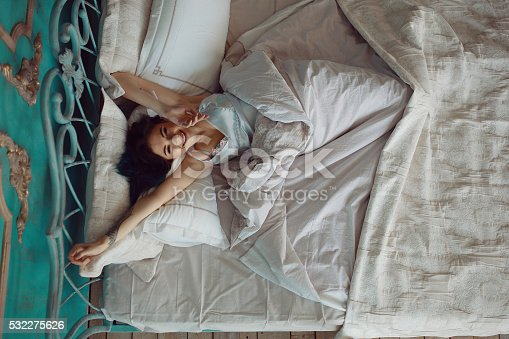 532275426 istock photo Woman stretching in bed after wake up 532275626