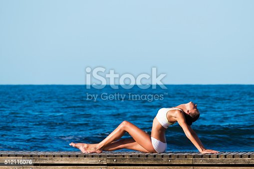 816941230 istock photo Woman stretching in exercise fitness training at coastline 512116076