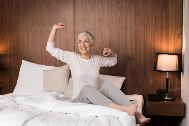 Woman stretching in her bed Cheerful senior woman with big beautiful smile waking up and stretching in her bedroom, Joy of the new day concept fresh start morning stock pictures, royalty-free photos & images
