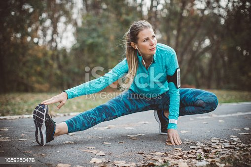 Adult running women stretching outdoor. She is preparing for hard training