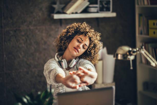 woman stretching in the office - fare una pausa foto e immagini stock