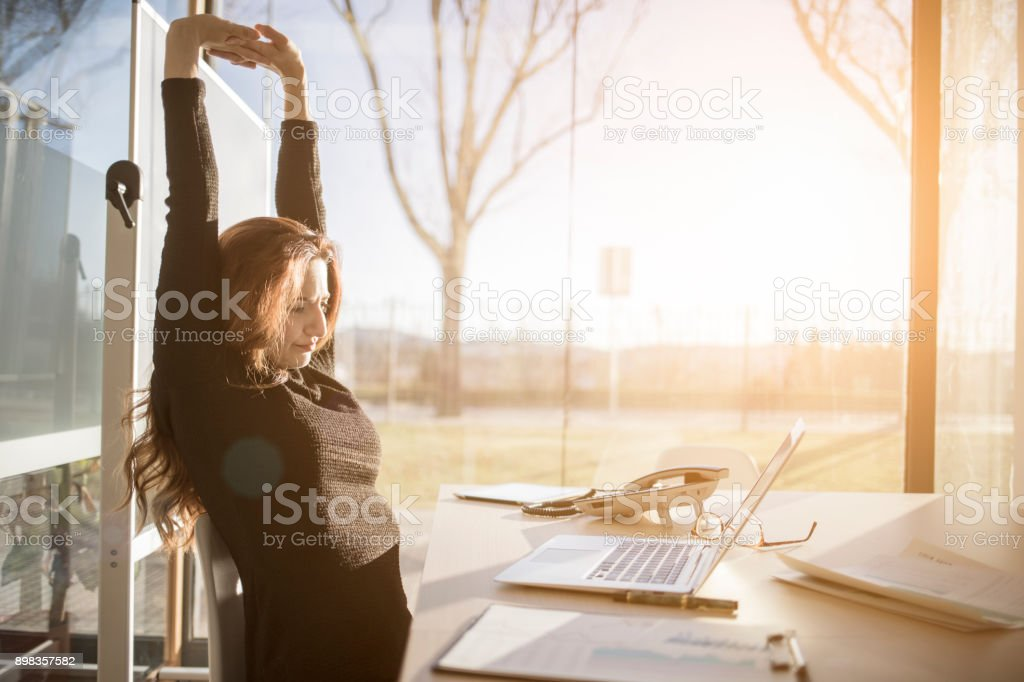 Woman stretching in the office stock photo