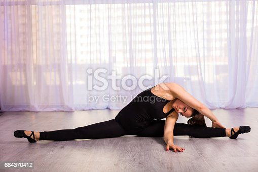 Pretty woman stretching in the fitness studio