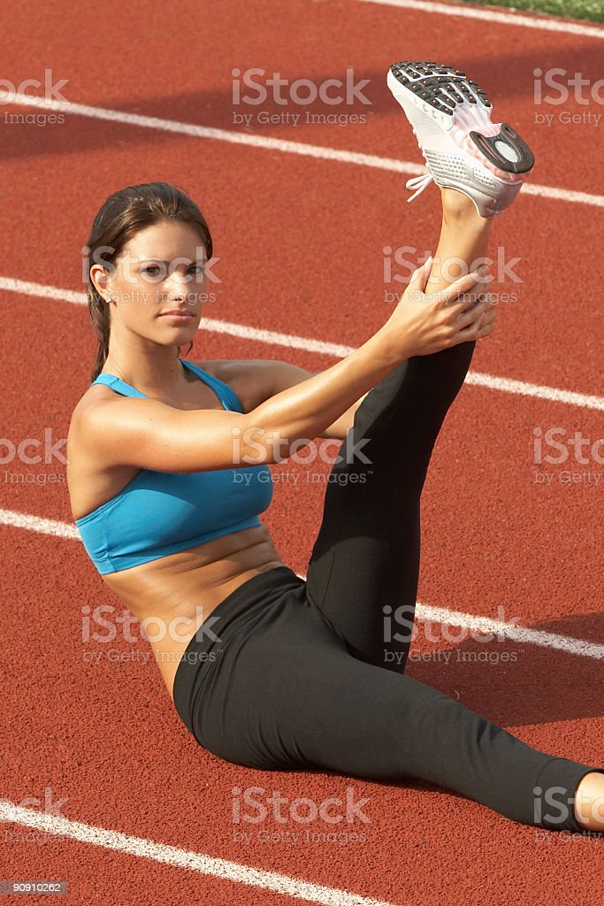 Woman Stretching Leg in the Air on Track stock photo