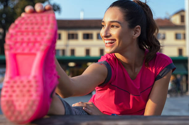 Woman stretching legs after running Young fitness woman runner stretching legs before run. Happy latin girl stretching her leg to warm up on the fence. Sporty woman warming up before outdoor workout in the street. touching toes stock pictures, royalty-free photos & images