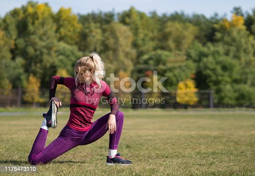 Fitness woman 20s stretching legs on a grass in park. Healthy lifestyle concept.