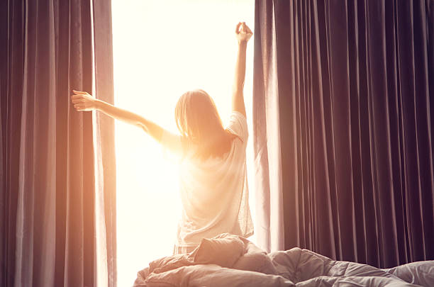 Woman stretching near bed after wake up Woman standing near the window while stretching near bed after waking up with sunrise at morning, back view routine stock pictures, royalty-free photos & images