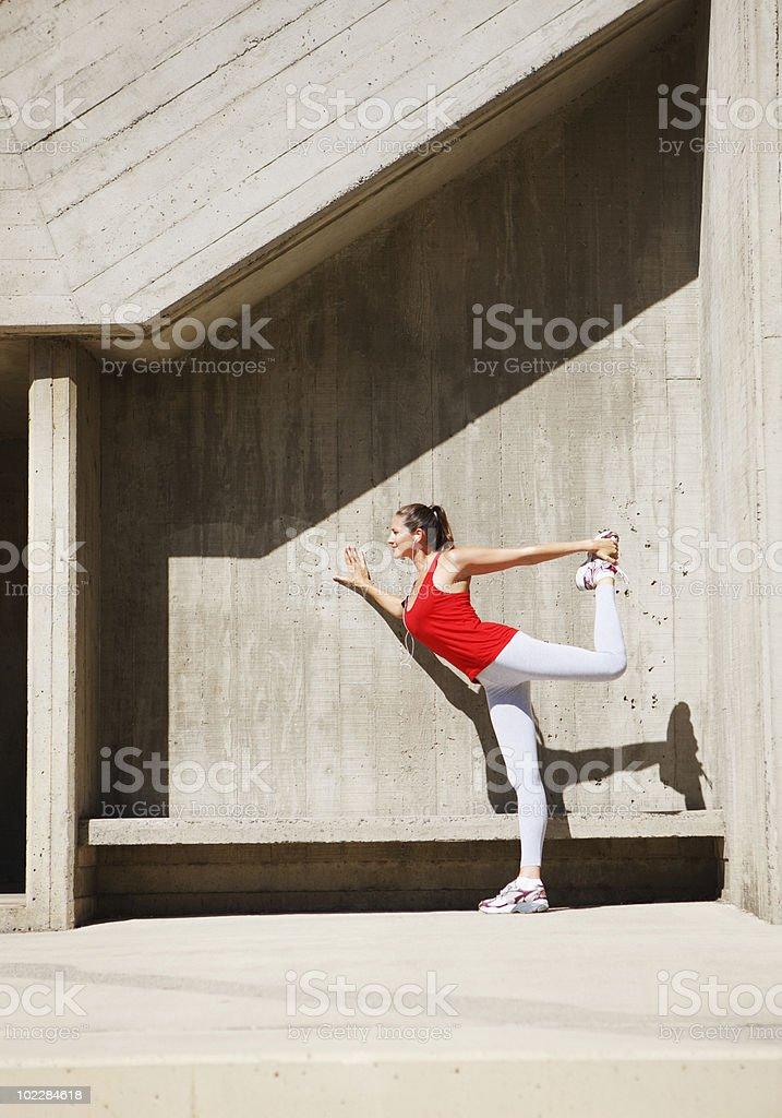 Woman stretching near concrete bench royalty-free stock photo