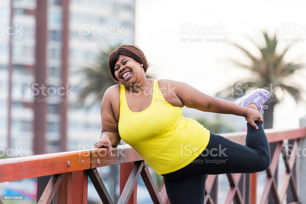 Woman stretching on a bridge stock photo