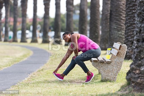 851958232 istock photo Woman stretching on a park bench 922786232