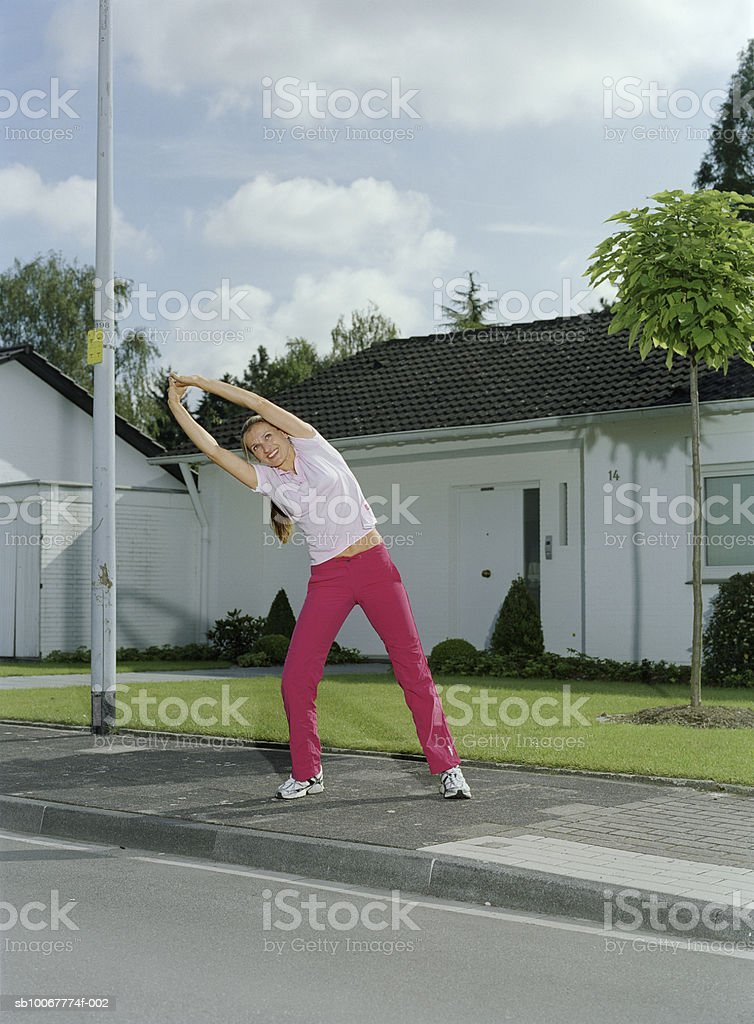 Woman stretching on pavement in suburbia foto stock royalty-free