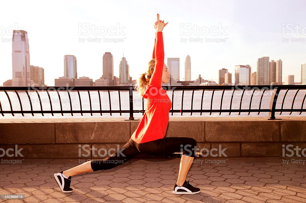 Woman stretching on sidewalks by water with cityscape royalty-free stock photo