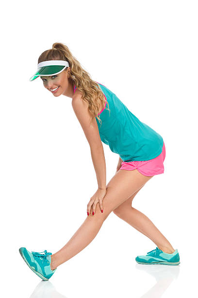 Woman Stretching Thigh With Standing Hamstring Stretch Exercise Smiling young woman in turquoise shirt, pink shorts, sneakers and green sun visor standing, holding hand on knee and stretching thigh, Side view. Full length studio shot isolated on white. hamstring stock pictures, royalty-free photos & images