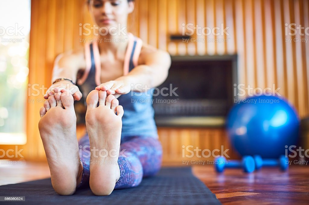 Woman stretching toe touch exercise on mat at home stock photo