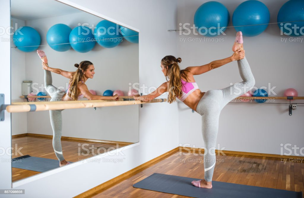Woman stretching using a barre stock photo