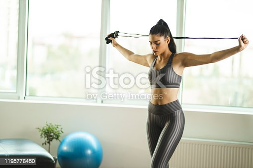 Fit woman stretching with jumping rope at home