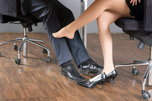 Woman stroking businessman's leg with her foot stock photo