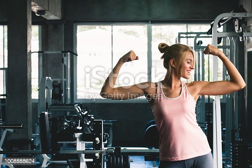 istock Woman strong posing  at sport gym weight training with happy smile feeling, gym workout concept 1008888624