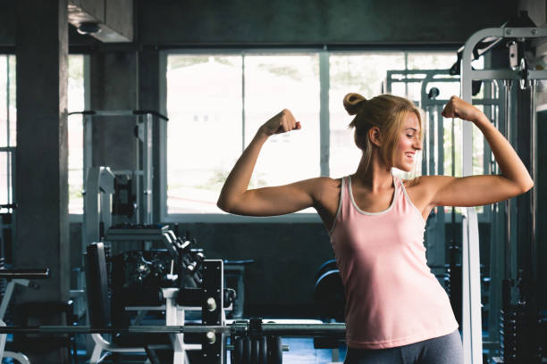 Woman strong posing  at sport gym weight training with happy smile feeling, gym workout concept stock photo
