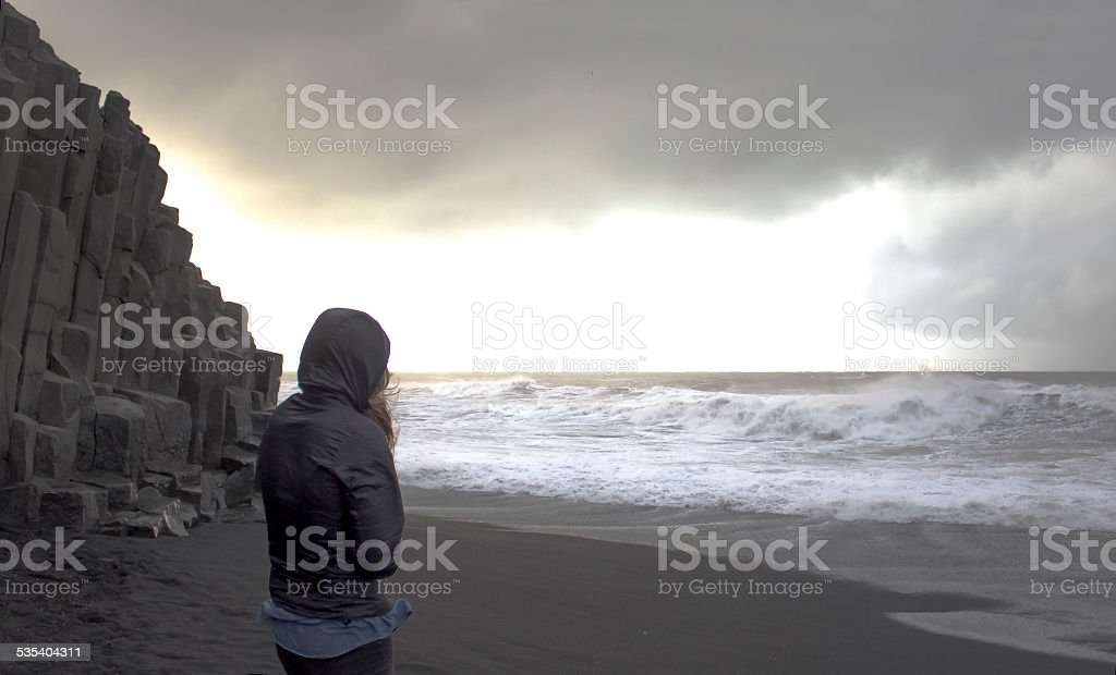 Woman struggles against wind at beach edge, volcanic landscape stock photo