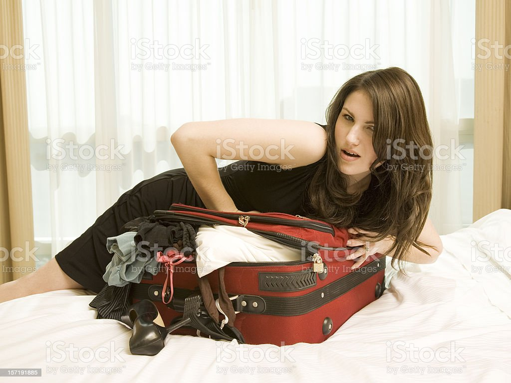 Woman Struggles to Close a Suitcase royalty-free stock photo