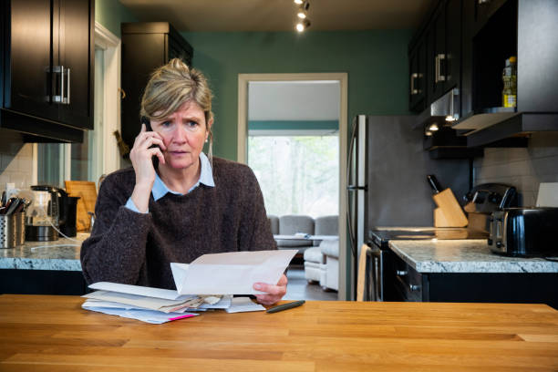 A woman struggling with home finances and debt. stock photo