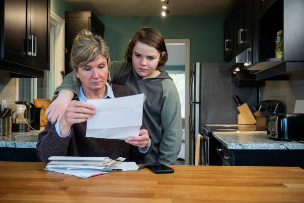 A woman struggling with home finances and debt while her son comforts her. stock photo