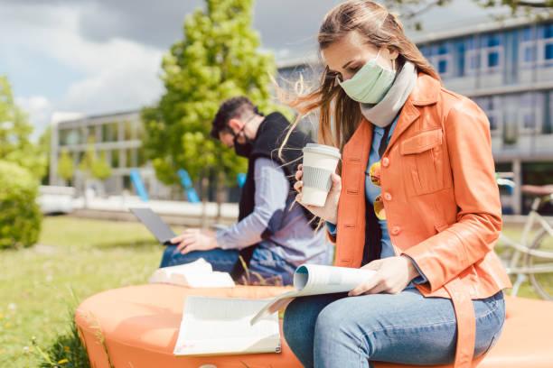mulher estudante no campus universitário aprendendo usando máscara facial - universidade - fotografias e filmes do acervo