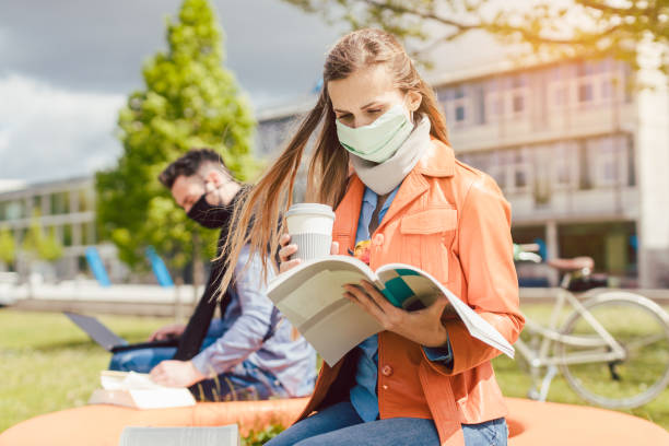 Woman student on college campus learning wearing face mask stock photo